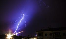 De reusachtige bout van bliksem raakt kleine stad stock afbeelding