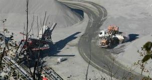 De reusachtige gele de ladingsstenen van de bulldozerbestelwagen in een vrachtwagen, gele bulldozer laadt graniet in de rug van e stock videobeelden