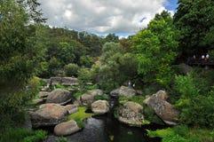De reusachtige keien liggen in de rivier onder hoge groene bomen tegen de blauwe hemel royalty-vrije stock foto