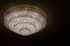 De reusachtige kroonluchters die van het kristalglas op balzaaldans hangen in de datum van de huwelijksceremonie Stock Fotografie