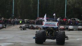 De reusachtige monstervrachtwagen die bij arena, verpletterende troepauto's omcirkelen, toont stock videobeelden