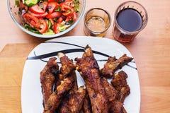 De ribben en de groenten van het barbecuevarkensvlees op witte plaat, sluiten omhoog mening stock fotografie
