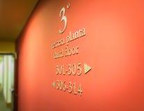 De richtingen van hoteltekens in een rode muur royalty-vrije stock fotografie