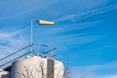 De Richtingsindicator van de luchtwind op Chemische Fabriek over Blauwe Hemel - luchtsok, remparachute, windkoker, windkegel Stock Foto's