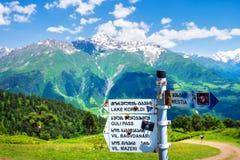 De richtingstekens op berg slepen voor toeristen in Mestia, Svaneti-gebied in Georgië stock foto's