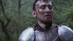 De ridder met vuil en bloed op zijn gezicht kijkt rond na de slag stock videobeelden