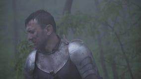 De ridder met vuil gezicht loopt na de slag in het rokerige bos stock video