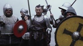 De ridder in metaalpantser houdt zijn zwaard en bevindt zich op het slagveld stock footage