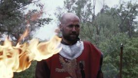 De ridder in rode stof over zijn pantser bevindt zich dichtbij de toorts stock video