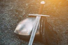 De ridder` s helm en het glanzende metaal die op de grond liggen, het zetten een oud staalzwaard met leerhandvat Stock Afbeelding