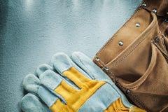 De riem beschermende handschoenen van het leerhulpmiddel op concrete achtergrond Stock Foto