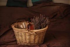 De rieten mand met droge lavendel bloeit, glazen en een fles wijn op het bed royalty-vrije stock afbeeldingen