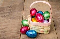 De rieten mand van Pasen met de eieren van de foliechocolade Royalty-vrije Stock Afbeelding