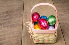 De rieten mand van Pasen met folieeieren Stock Afbeeldingen