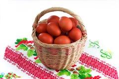 De rieten mand van Pasen met rode paaseieren op een witte achtergrond stock fotografie