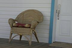 De rieten stoel is op de portiek door de deur stock afbeelding