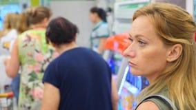 De rij van mensen die zich bij de controle in de supermarkt bevinden 4k, langzame motie stock videobeelden