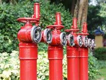 De rij van rode brandkranen, steekt hoofdpijpen, pijpen voor brandbestrijding in brand en brandblus Stock Foto