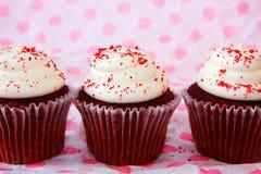 De rij van rood fluweel cupcakes met rood bestrooit stock afbeeldingen