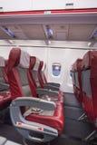 De rij van rood zit in vliegtuig en venster Stock Foto