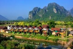 De rij van toeristenbungalowwen langs Nam Song River in Vang Vieng, wedijvert Stock Foto