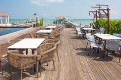 De rijen van houten stoel en lijst bepalen van op terras van restaurant met zeegezicht op de achtergrond de plaats Royalty-vrije Stock Afbeelding