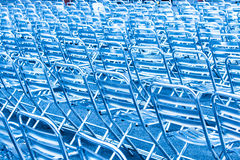 De rijen van leeg metaal zitten zetels in blauw licht voor Stock Foto's