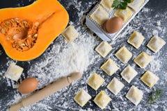 De rijen van pompoenen ruwe eigengemaakte ravioli op een donkere achtergrond met ingrediënten, sluiten omhoog en hoogste mening stock fotografie