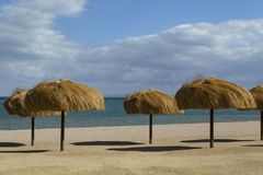 De rijen van stroparaplu's op een verlaten strand Stock Afbeelding