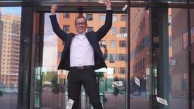 De rijke aantrekkelijke Zakenman in glazen neemt geld op en verheugt zich Langzame Motie stock footage