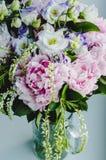 De rijke bos van roze pioenenpioen en lilac eustomarozen bloeit in glasvaas op witte achtergrond Rustieke stijl, stilleven Royalty-vrije Stock Afbeelding
