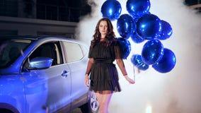 De rijke dame in in kleding met opblaasbare ballons die zich dichtbij machine in rook onder het vliegen bevinden fonkelt stock videobeelden