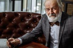 De rijke oude prettige mens bekijkt camera close-up bebouwde foto royalty-vrije stock afbeeldingen