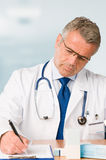De rijpe arts schrijft medisch examen voor stock foto