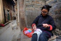 De rijpe Aziatische ontwerpen van het vrouwenborduurwerk op stof, Guizhou Provin stock afbeeldingen