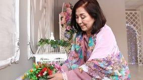 De rijpe Aziatische vrouw zorgt voor de bloemen stock videobeelden