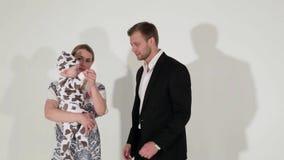 De rijpe blauw-eyed man in kostuum bevindt zich naast vrouw die baby in handen houdt stock videobeelden