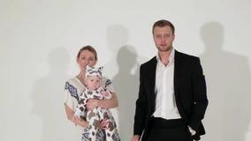 De rijpe blauw-eyed man in kostuum danst met vrouw die baby in handen houdt stock video