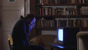 De rijpe donkerbruine mensenzitting op kleine kruk behandelt gezicht met handen en staat op stock footage