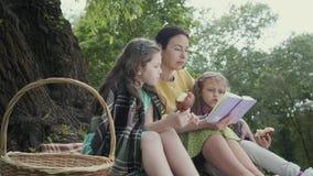 De rijpe grootmoeder zit in het park dichtbij boom op de algemene lezing een boek met twee kleindochters die eatting smakelijk stock videobeelden