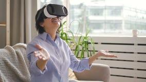 De rijpe hogere vrouw gebruikt virtuele werkelijkheidsglazen zittend op laag in flat stock footage