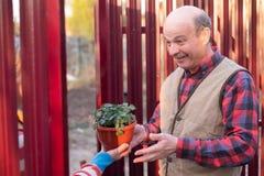 De rijpe Kaukasische mens is gelukkig om een gift van buur te ontvangen royalty-vrije stock foto's