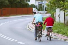 De rijpe man en de vrouw berijden een fiets onder greens Een gezond en actief deel van het leven Ecologisch vervoer voor de bevol royalty-vrije stock foto's