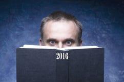 De rijpe mens die door boek worden geconcentreerd en wordt vastgehaakt, die open boek lezen, verraste de jonge mens, die ogen ver Stock Afbeeldingen