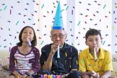 De rijpe mens en de kleinkinderen vieren verjaardag royalty-vrije stock afbeeldingen