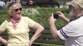 De rijpe mens fotografeert zijn modieuze mooie vrouw bij de bank in park stock videobeelden