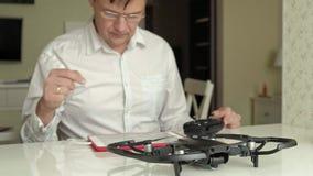 De rijpe mens in glazen en een wit overhemd assembleert een quadrocopter, verbindt de controles, het concept het leren stock footage