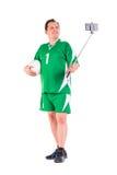 De rijpe mens kleedde zich in het groene sportkleding stellen Stock Afbeeldingen