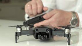 De rijpe mens met glazen en een wit overhemd assembleert een controlebord voor een quadrocopter, een concept voor de studie van stock footage
