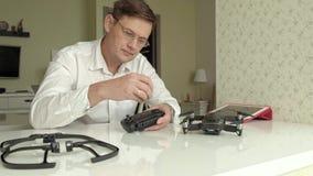 De rijpe mens met glazen en een wit overhemd assembleert een controlebord voor een quadrocopter, een concept voor de studie van stock video